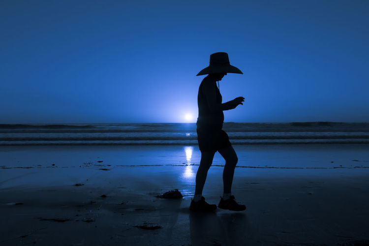 Man silhouetted walks on the beach sand in California. Blue color added in post processing Travel Beach Beauty In Nature Blue Blue Sky Full Length Horizon Over Water Leisure Activity Lifestyles Men Nature One Person Outdoors People Real People Sandiego Scenics Sea Silhouette Sky Standing Sunset Travel Blog Vacation Water