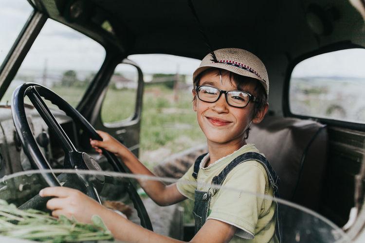 Portrait of boy holding steering wheel sitting in car