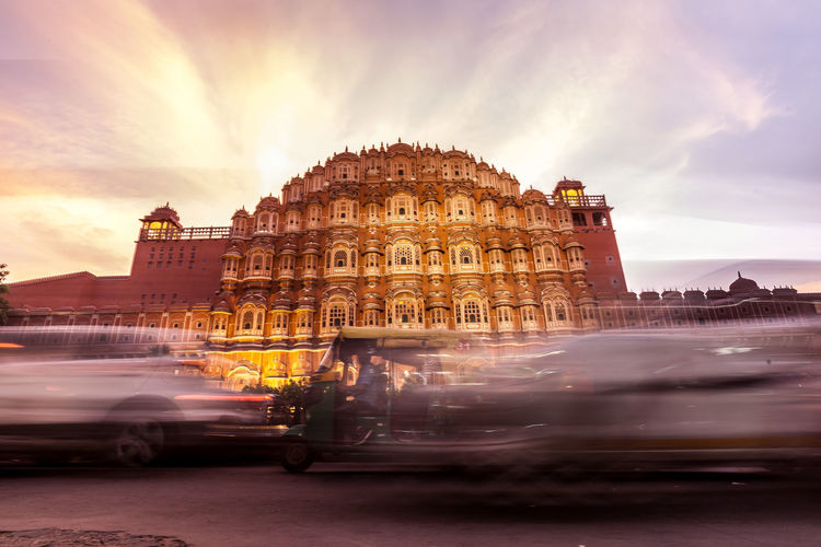 Blurred motion of jinrikisha by hawa mahal against cloudy sky
