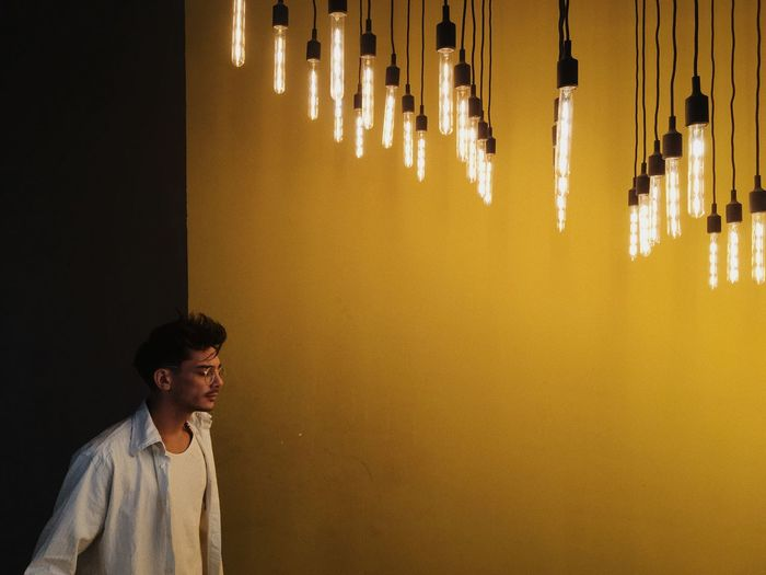 Man standing under illuminated pendant lights in home
