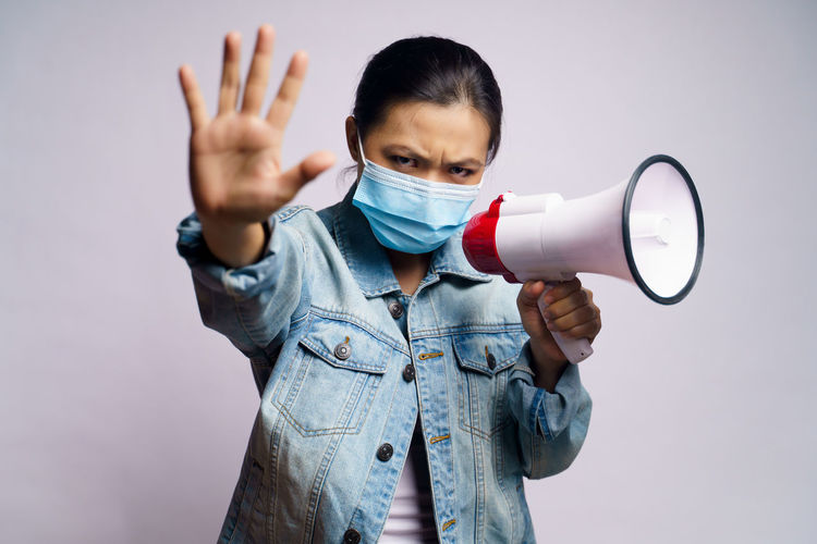 Portrait of young woman wearing flu mask holding megaphone standing against gray background