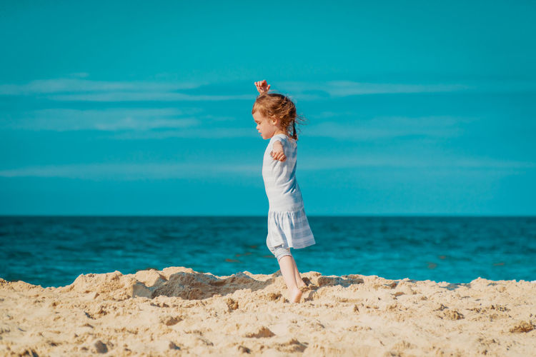 Summer Child Girl Kid Sea Beach Water Sky One Person Land Full Length Horizon Over Water Horizon Human Arm Leisure Activity Day Nature Standing Side View Limb Lifestyles Sand Arms Raised Hairstyle Outdoors Freedom