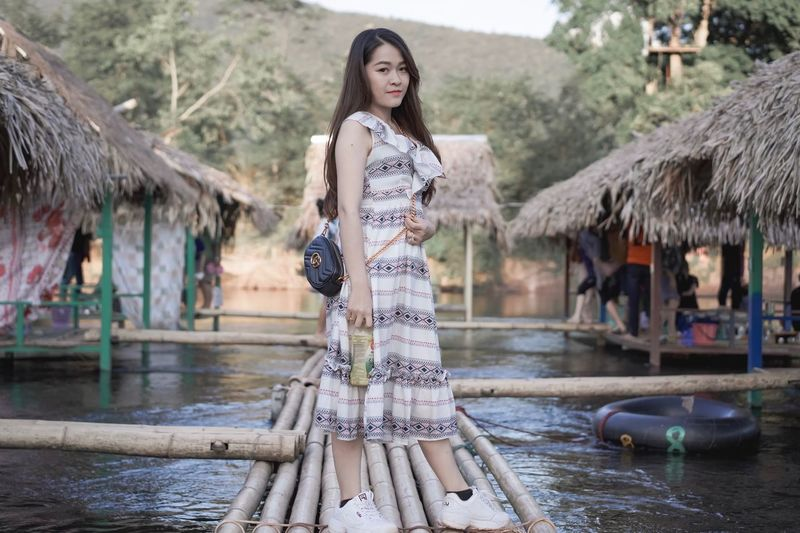 Full length of woman standing on walkway over lake