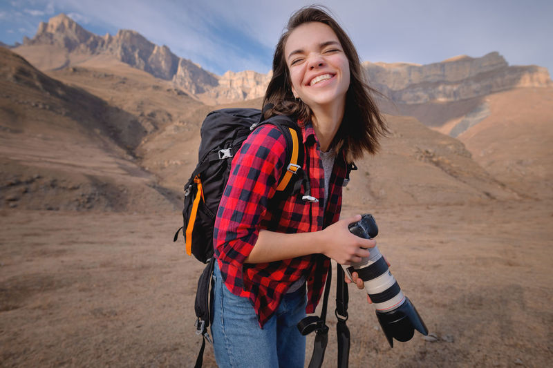 Smiling young woman standing on mountain road