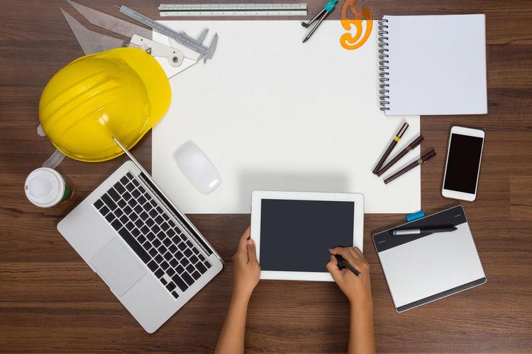 Cropped hands of architect using digital tablet at desk