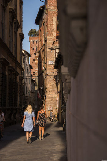 Lucca Italy Adult Alley Architecture Building Building Exterior Built Structure Casual Clothing City Day Full Length Incidental People Leisure Activity Lifestyles Men People Real People Rear View Street Two People Walking Women
