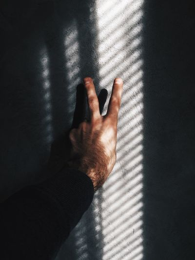 Man hand showing peace sign on wall with shadow