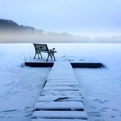 Pier on frozen lake against sky during winter