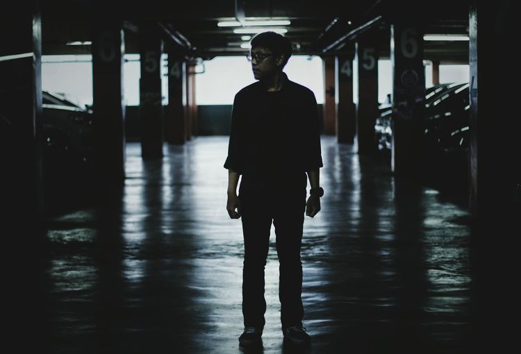 Full length of man looking away while standing in parking lot