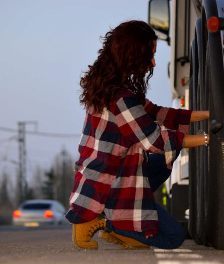 Side view of young woman holding railing on road
