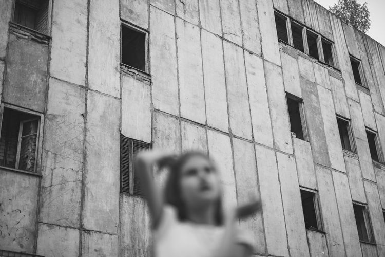 Low angle view of girl standing against building