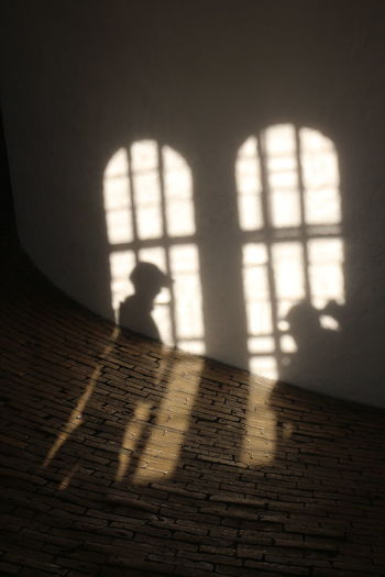 Shadow of woman walking on window