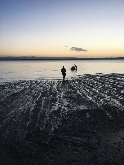 Silhouette male friends with jet boat in sea during sunset