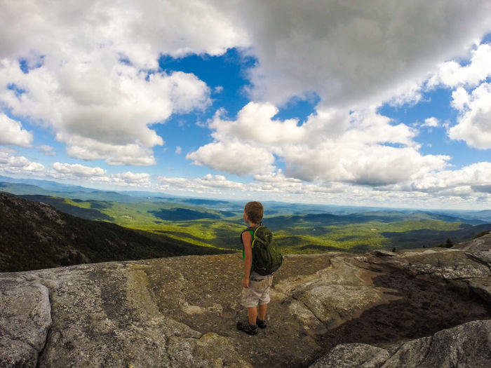 Rear View Of Boy Standing On Rocky Mountain Peak While Looking At Landscape Against Sky