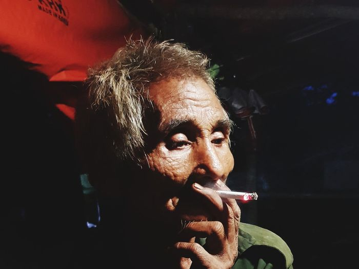 Close-Up Of Senior Man Smoking Cigarette