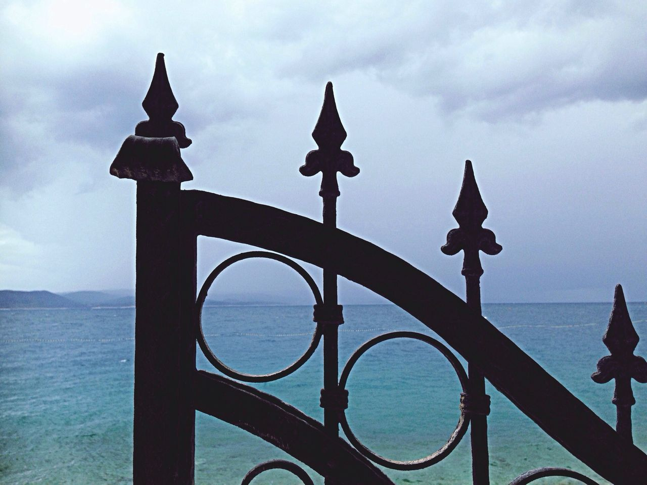 Metal Gate Against Sea And Cloudy Sky