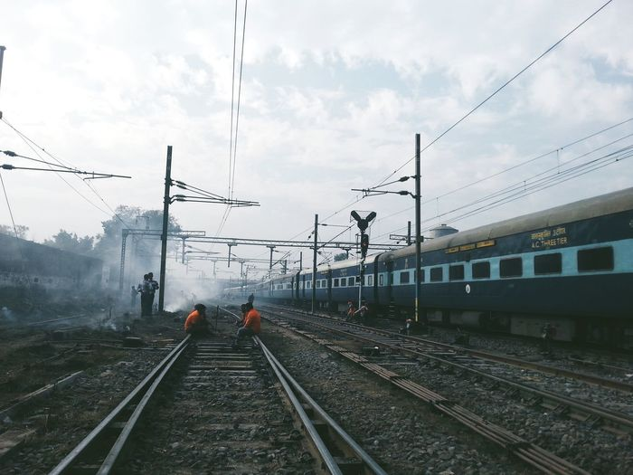 Men repairing railroad tracks against sky