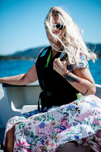 Mid adult woman wearing sunglasses while sitting in boat on lake against clear blue sky