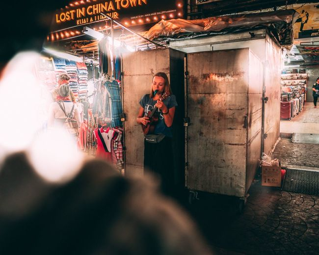 Young Woman Singing While Standing In Market At Night