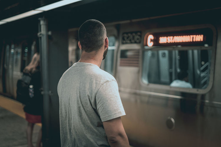 Rear view of man standing at train