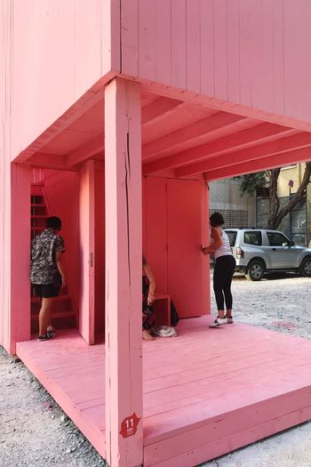 Rear view of man standing by pink building