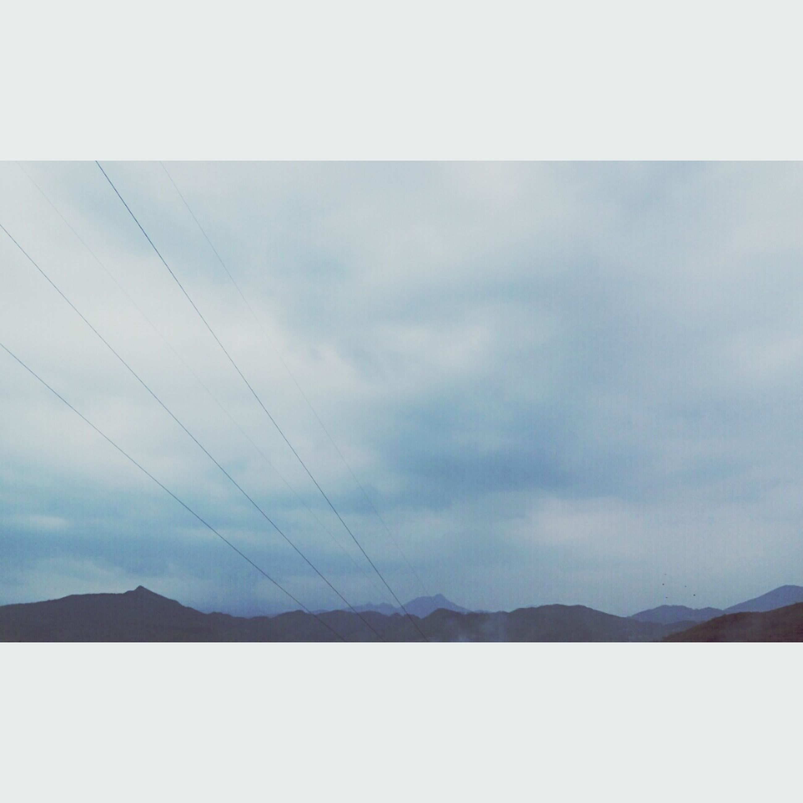 sky, transfer print, cloud - sky, low angle view, power line, tranquility, scenics, tranquil scene, auto post production filter, cloudy, beauty in nature, nature, cloud, mountain, connection, electricity pylon, cable, outdoors, weather, no people