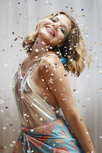 Smiling Young Woman Standing Amidst Confetti In Party