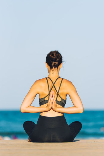 Rear view of mid adult woman meditating at beach against clear sky