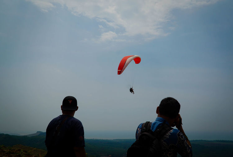 Rear view of people paragliding against sky