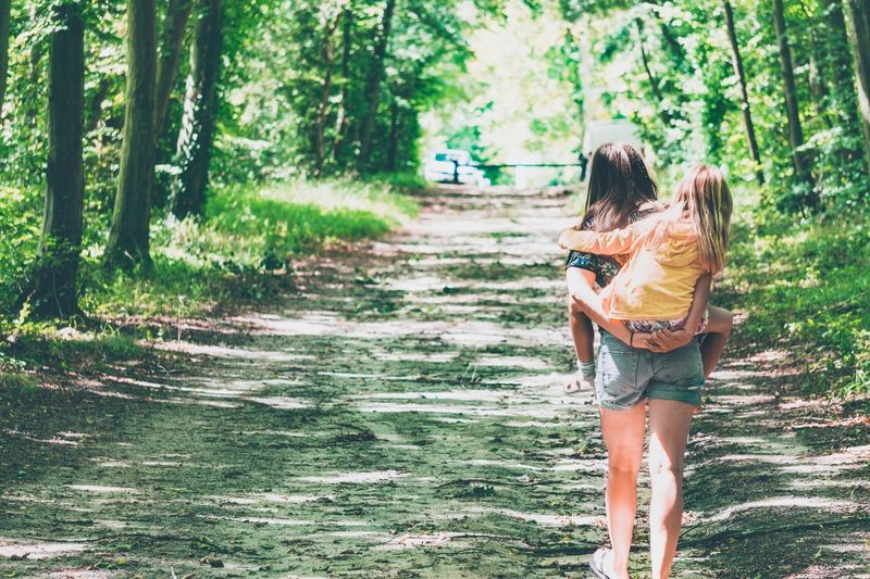 Rear View Of Mother Piggybacking Daughter While Walking In Forest