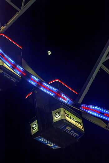 Low angle view of illuminated text against sky at night