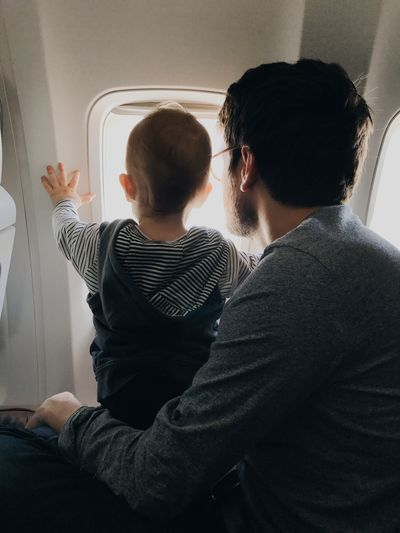 Parenting Family Togetherness Father And Son Son Child Window Light Window Toddler  Destinations Traveling Travels Airplane Men Indoors  Two People Real People Lifestyles Togetherness Casual Clothing Emotion Sitting Adult People Love Communication Young Adult Young Men Males