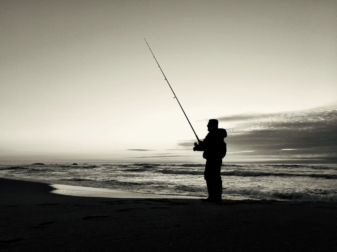 Silhouette Man With Fishing Rod At Beach