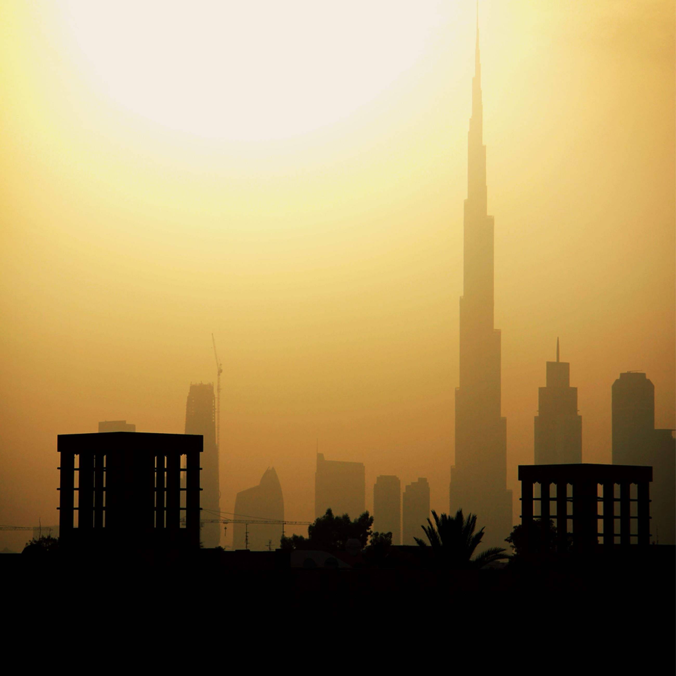 architecture, building exterior, sunset, built structure, silhouette, sun, city, orange color, tower, skyscraper, sky, tall - high, building, copy space, sunlight, clear sky, outdoors, no people, urban skyline, modern