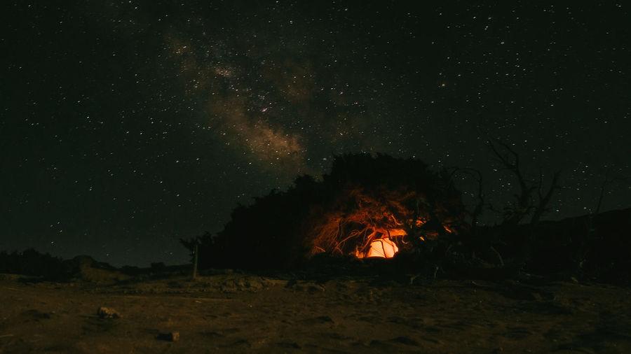 Bonfire on field against sky at night