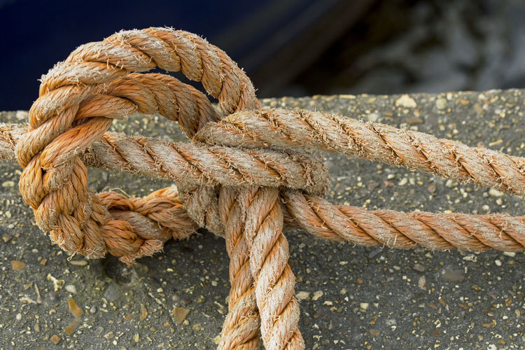 Close-up of rope tied on retaining wall
