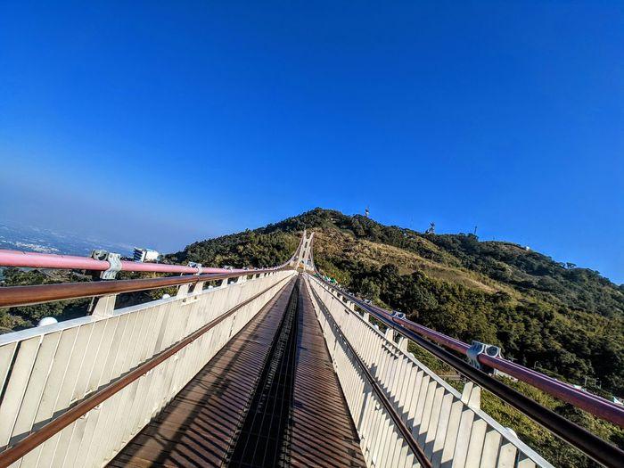Footbridge over road against clear blue sky
