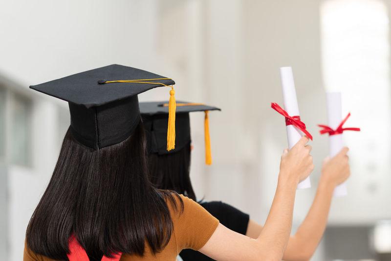 Rear view of women holding certificate