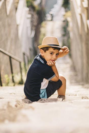 Portrait of boy wearing hat sitting on steps