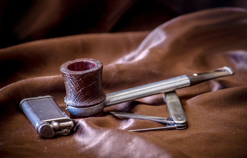 Close-up of smoking pipe by cigarette lighter with hand tool on brown leather