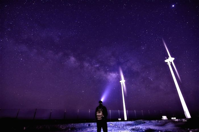 Man with flashlight standing against star field on field