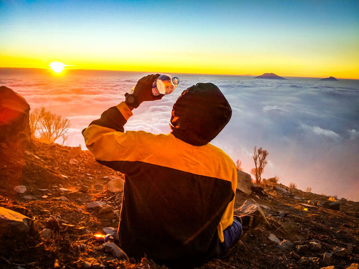 Rear view of man on mountain during sunset