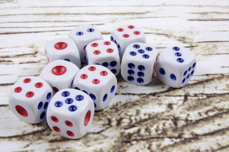 DICES ON A WOODEN TABLE Arts Culture And Entertainment Close-up Cube Shape Dice Gambling Game Of Chance Group Of Objects High Angle View Indoors  Leisure Activity Leisure Games Luck Medium Group Of Objects No People Opportunity Relaxation Spotted Still Life Table White Color Wood - Material