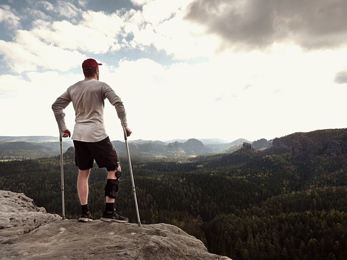 Hiker in t-shirt, medicine crutch and leg fixed in immobilize.  man has broken leg in immobilizer