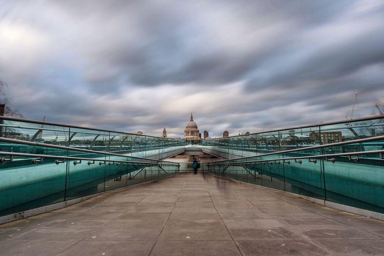 Diminishing view of london millennium footbridge against cloudy sky