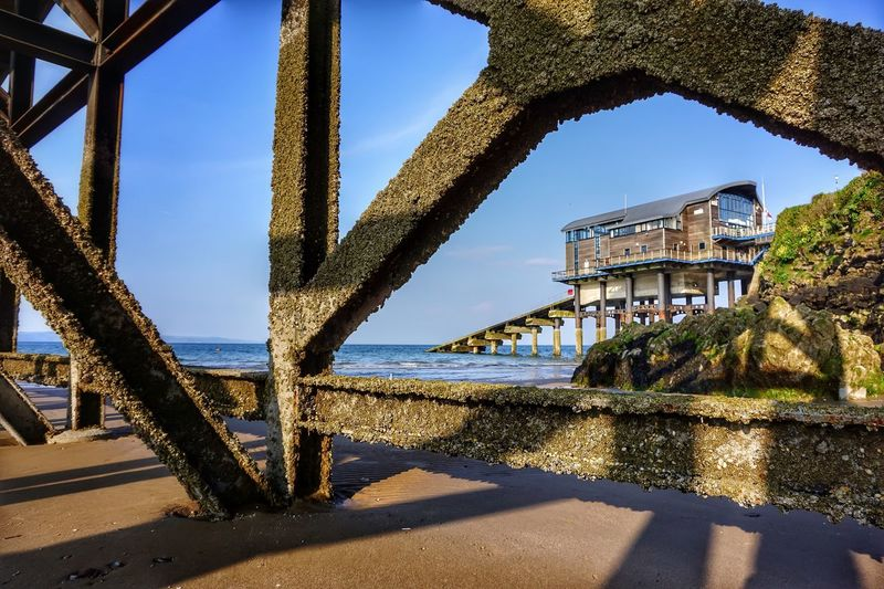 Low angle view of built structure lifeboat station against blue sky