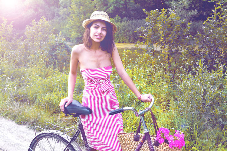 Portrait of young woman standing with bicycle by plants