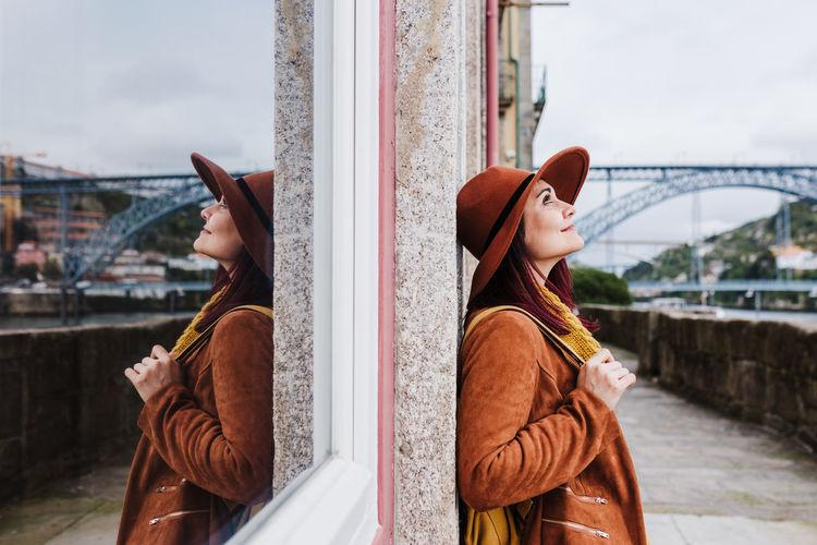 Woman wearing hat against sky in city