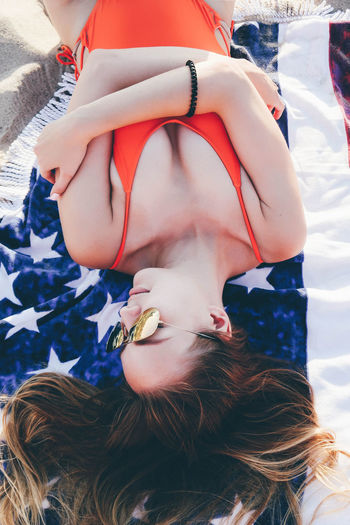 High angle view of young woman wearing sunglasses while lying on blanket at beach