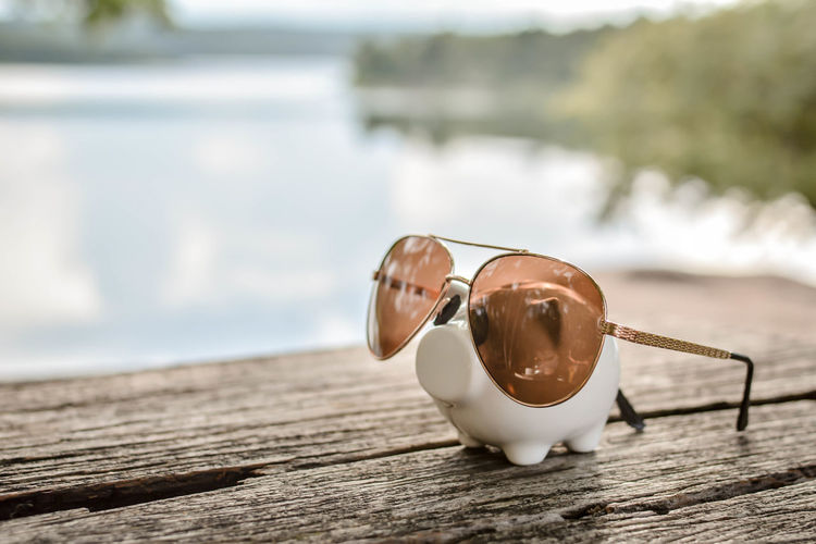 Close-up of sunglasses with piggy bank on wooden table against lake